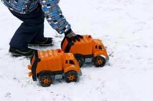 Child playing with trucks in snow